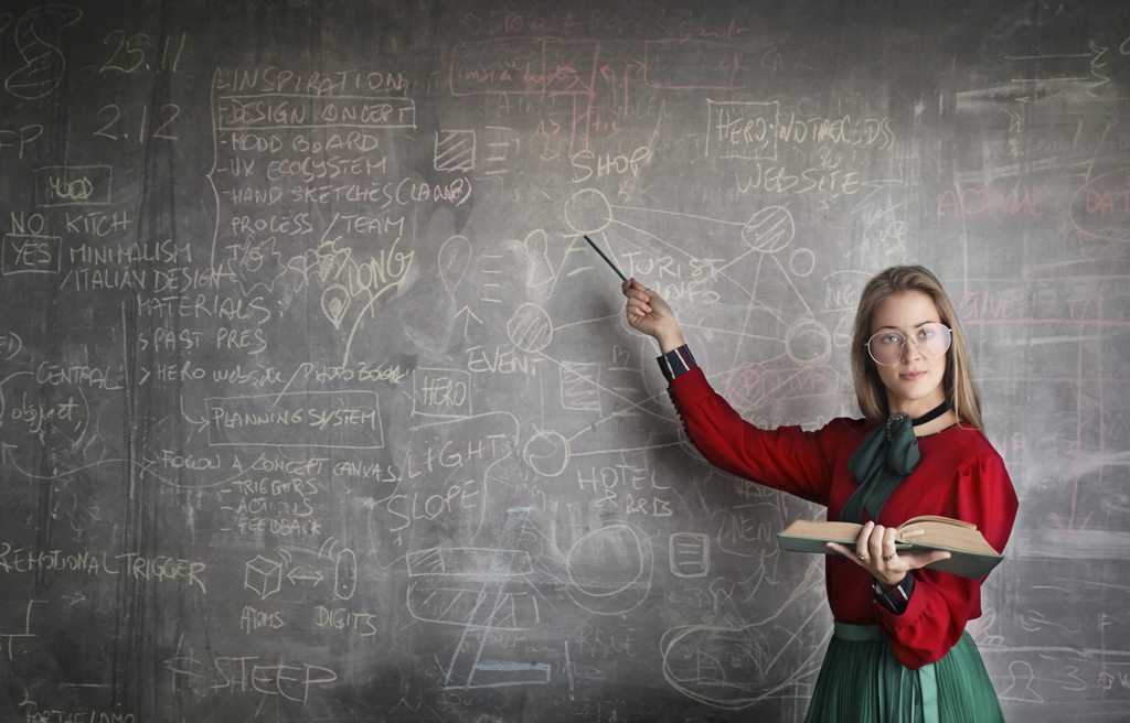 strict-female-teacher-with-book-pointing-at-scribbled-3771074